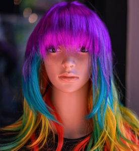 A mannequin with multicoloured hair; a purple fringe, a layer of aqua around the face, with yellow and red at the bottom, representing the limited affect Colourless will have on Fashion/non oxidised colours